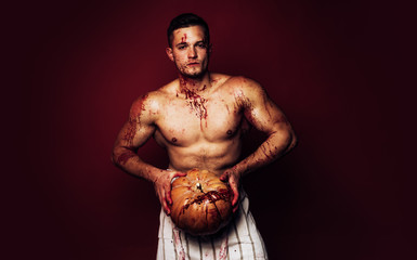 Muscular Vampire butcher man with blood. Man with serious face and naked torso on red background. Halloween man with a carved Pumpkin. Dark background.