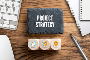 """Word """"project strategy"""" on slate plate and cubes with symbols for project management at a workplace"""