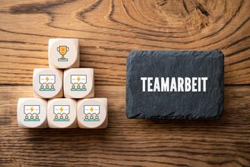 """Schiefertafel mit Wort """"Teamarbeit"""" und Würfel mit Team-Symbolen"""