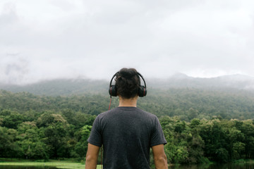 Man with headphones back view. looks into the distance with nature in the horizon.Amidst the beautiful nature.