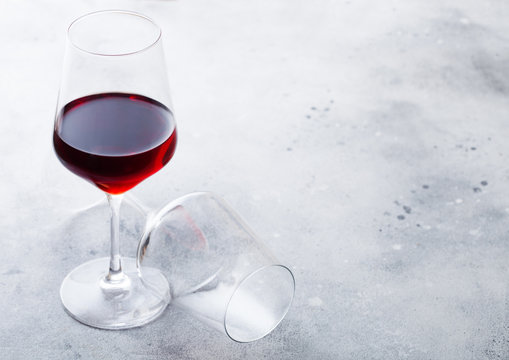 Elegant glasses of red wine on stone kitchen table background.