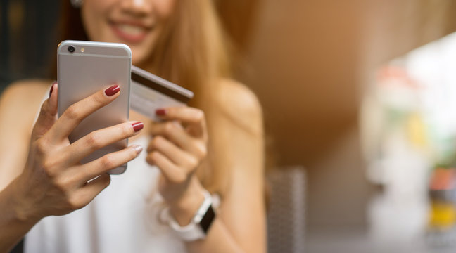 close up asian business woman holding smartphone with credit card for pay online shopping e-commerce concept