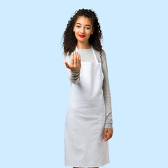Young girl with apron presenting and inviting to come on isolated blue background