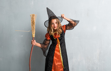 Little girl dressed as a witch and holding a broom for halloween holidays making victory gesture Wall mural