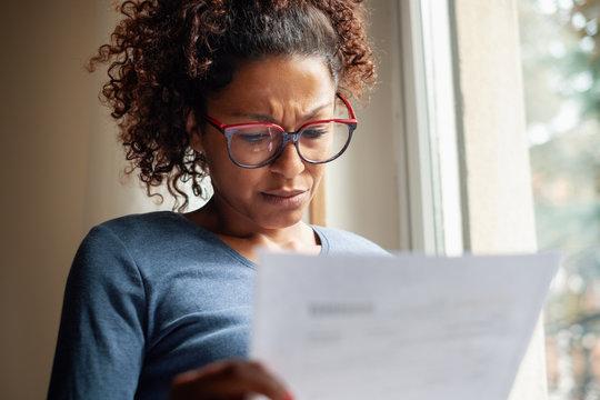 Sad black woman near window reading bad news letter