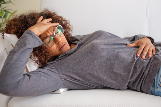 Woman feeling pain to the stomach lying on sofa