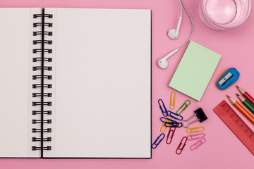 Open school notebook for your text over colorful supplies on pink background. Back to school concept with copy space. Flat lay. Top view.