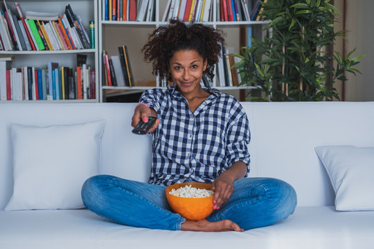 Black woman watching tv at home and holding a remote control