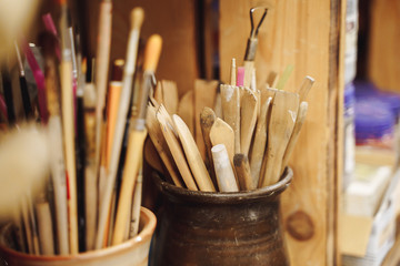 Set of brushes and painting tools on table in artist's workshop