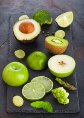 Fresh raw organic green toned fruit and vegetables on stone board black background. Avocado, lime, apple, kiwi and grapes with broccoli and cauliflower. Top view