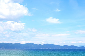Beautiful minimalistic seascape of calm sea, sandy beach, blue sky, Greece. Horizontal.