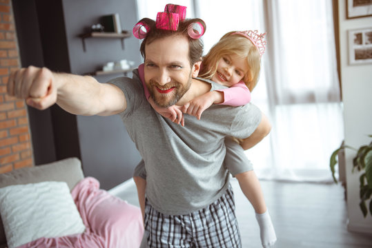I am superman. Portrait of happy father is carrying his daughter on back and laughing. He is stretching hand forward. Man has make-up on face and hair curlers
