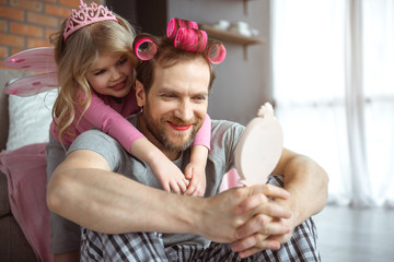 Portrait of joyful dad is looking at result of playing with girl. He is holding mirror and smiling while having facial makeup. His daughter is standing behind and embracing man with love