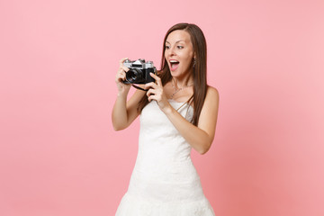 Amazed bride woman in wedding dress taking pictures on retro vintage photo camera choosing staff, photographer isolated on pink background. Wedding to do list. Organization of celebration. Copy space.