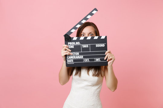 Shocked bride woman in wedding dress hiding covering face with classic black film making clapperboard isolated on pastel pink background. Wedding to do list. Organization of celebration. Copy space.