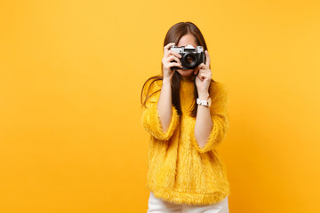 Brunette young woman in fur sweater covering face and taking pictures on retro vintage photo camera isolated on bright yellow background. People sincere emotions, lifestyle concept. Advertising area.