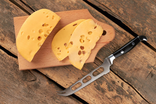 Traditional Dutch cheese with holes. Slices of Maasdam chees and knife on vintage wooden boards. Healthy dairy product.