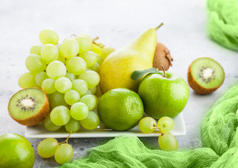 Fresh raw organic green toned fruit on white ceramic square plate on stone kitchen table background. Pear and grapes with kiwi and lime and apples.