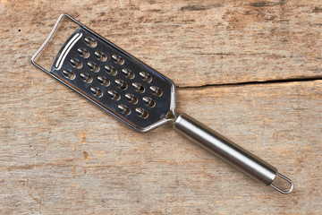Cheese grater on wooden background. Stainless steel grater on vintage wooden background. Sharp kitchen utensil.