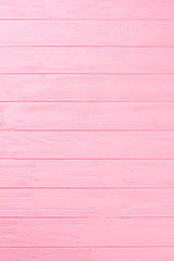 Wooden textured background. Pink striped wooden boards, vertical image. Painted wooden wall close up.