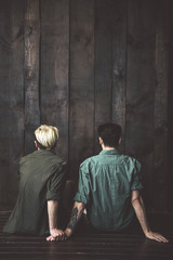 Back view portrait of two loving young men holding hands on wooden background