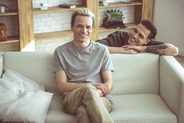 Look at me. Toned portrait of blond handsome guy sitting on couch while his boyfriend standing behind and gazing at him with smile
