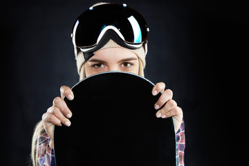 People, travel, recreation and extreme sports concept. Portrait of mysterious positive young woman snowboarder with protective goggles on her head, hiding behind black board and looking at camera