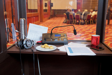 Translator room . translators cubicle . interpreting - Microphone and switchboard in an simultaneous interpreter booth . Soft focus of wireless Conference microphones and notebook in a meeting room.