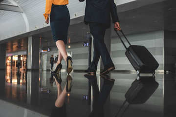 Woman and man going ahead. Businessman carrying suitcase on wheels