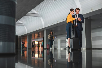 Full length portrait of concentrated couple standing in corridor and typing on smartphone screen. Copy space on left side