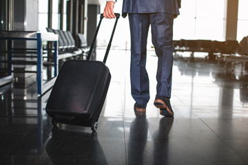 Businessman carrying suitcase on wheels and walking ahead. Focus on male legs