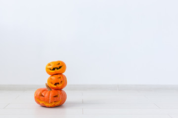 Jack-o-lantern carved pumpkin on light wall background with copy space, autumn and halloween home decor