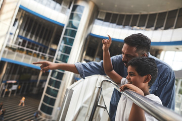 Cheerful Hindu boy standing near handrail with his father who is showing him the airport