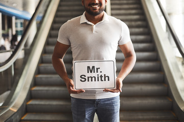 Positive smiling hindu man holding a sign with a name while standing in the airport