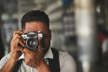 Pleasant Hindu man making professional shots while enjoying photography practice