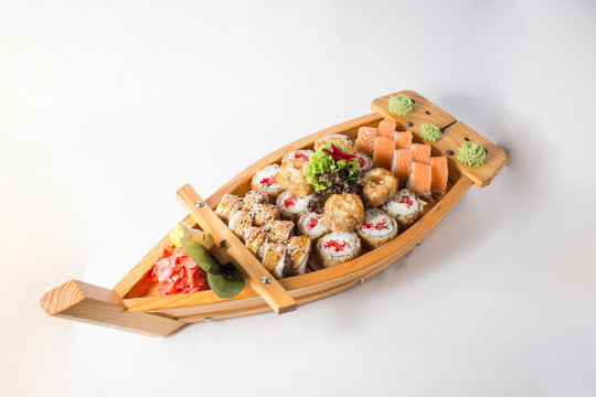 Wooden boat with lots of sushi with ginger and wasabi