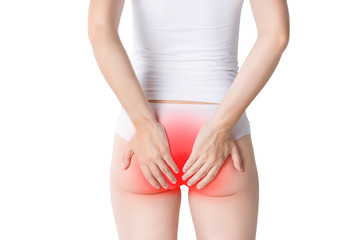 Woman suffering from hemorrhoids, anal pain on gray background
