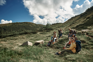 Happy five tourists with rucksacks walking to mount top together. Four women and man sitting on ground and resting before continuing climbing