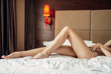 Sexy woman with bare breasts lying in bed