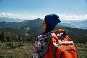 Tranquil woman is standing with rucksack while wearing sunglasses. She is hiking and enjoying view of high peaks and nature around female backpacker is spending time in mountains