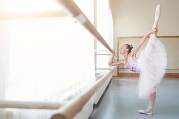 Ballerina in tutu stretching leg in class