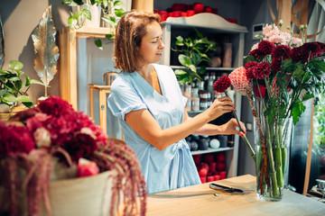 Female florist puts flowers in a vase, floral shop