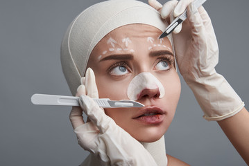 Terrified patient. Emotional nervous woman frowning and looking at the scalpel while having bandages on her head