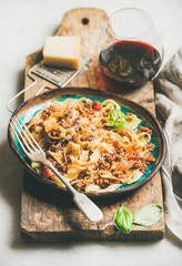Italian traditional pasta dinner. Tagliatelle bolognese with minced meat, tomato sauce and parmesan cheese and glass of red wine over rustic wooden board, selective focus
