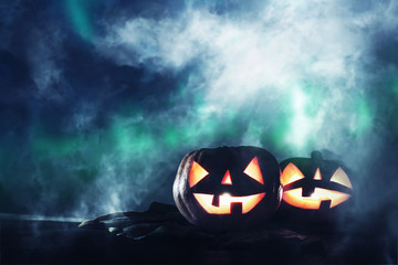 Halloween holiday concept. Pumpkins over wooden table at night scary, haunted and misty forest.