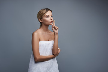 Lovely young lady looking pretty in her white towel and putting one finger to the lips while standing against the grey background