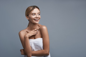 Positive emotional young lady standing against the grey background and laughing happily while wearing her white towel
