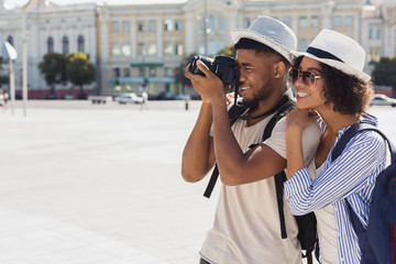 African-american tourist couple taking photos on camera on street