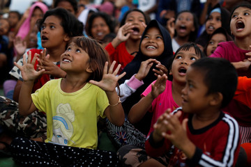 Children gather to received occupational therapy at a camp for displaced victims of the earthquake and tsunami in Palu