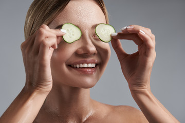 Cucumbers on the eyes. Cheerful emotional young lady standing against the grey background with naked shoulders and putting pieces of cucumbers on the eyes